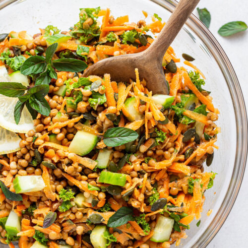 overhead of lentil salad with carrots served in a clear glass bowl with wooden spoon