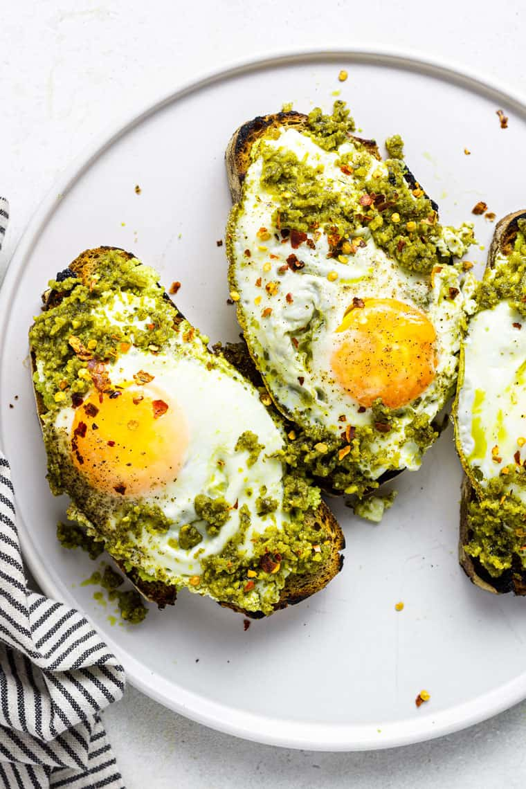 close up on toast topped with pesto and fried eggs