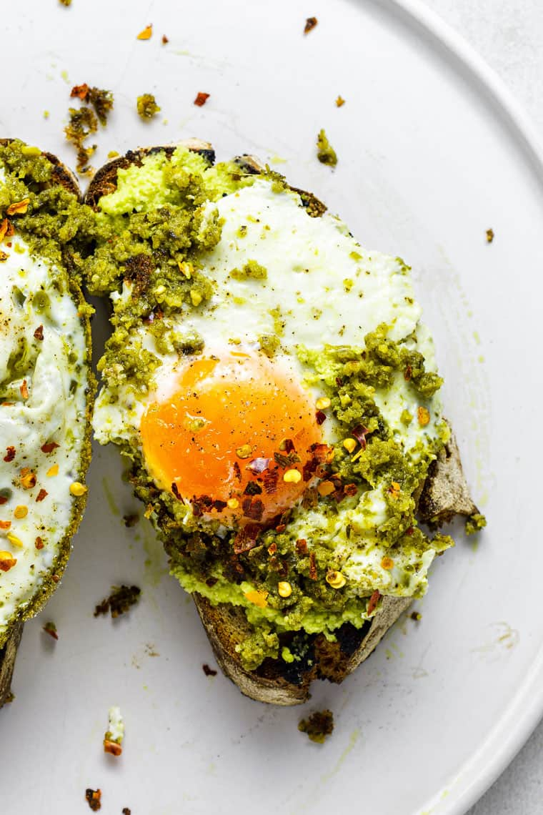 close up on a slice of toast with pesto and a fried egg with red pepper flakes