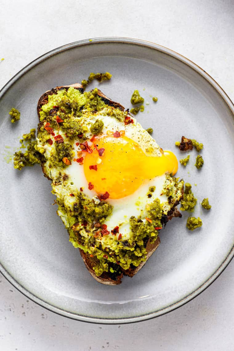 plate with a slice of toast and pesto egg on top