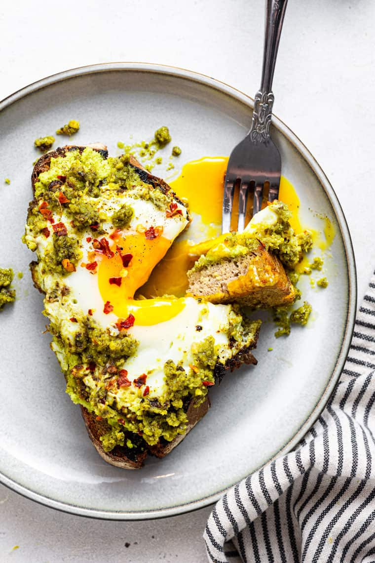 fork taking a bite of pesto egg toast with a soft yolk