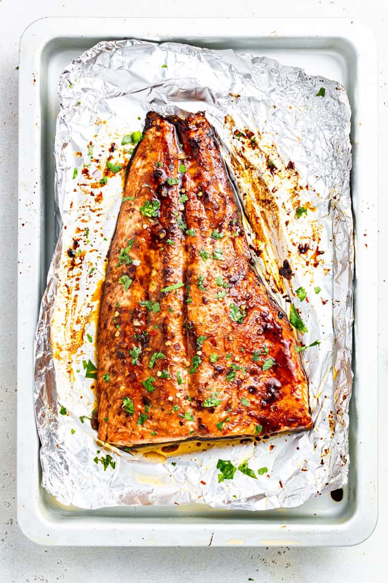 cooked side of salmon on a piece of foil with green herbs on top