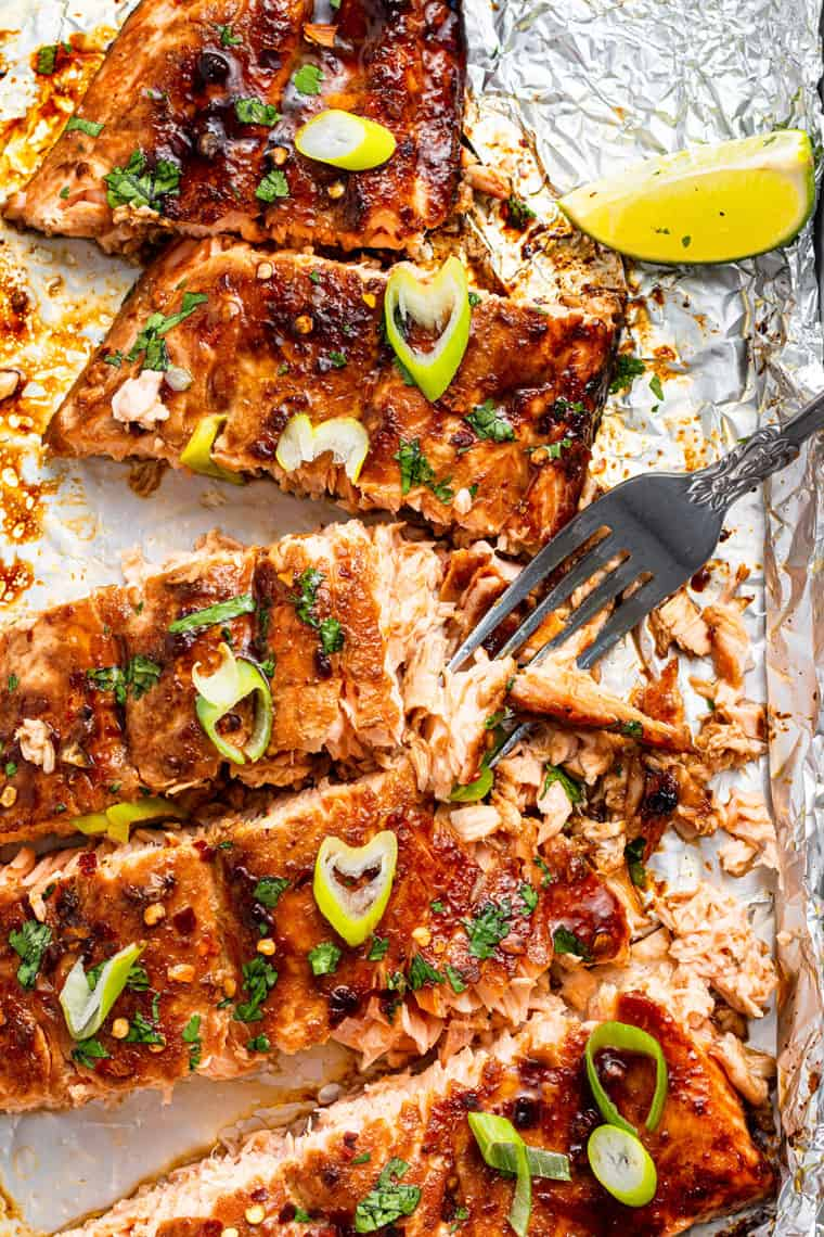 slices of spicy salmon on a piece of foil with scallions on top