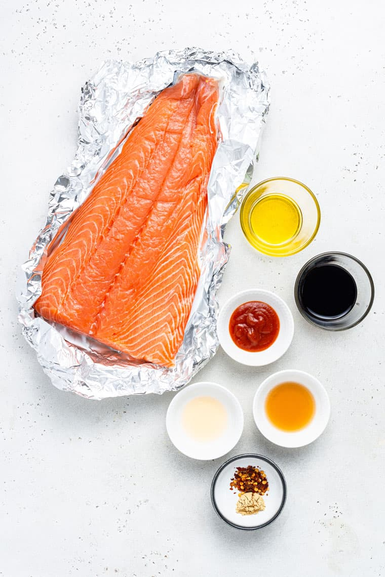 large piece of salmon in a foil wrapper with ingredients for sauce in small bowls on the side