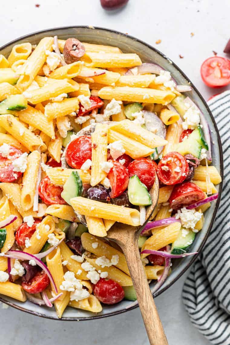 stirring pasta salad with raw vegetables and olives