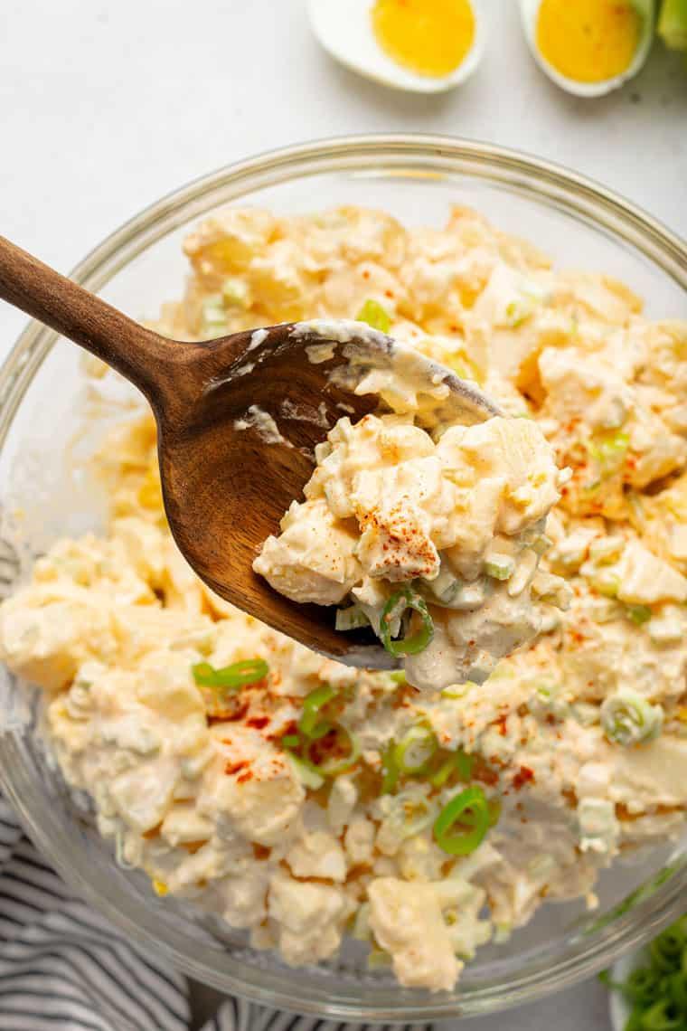 spoon holding a scoop of potaot salad over a bowl of potato salad