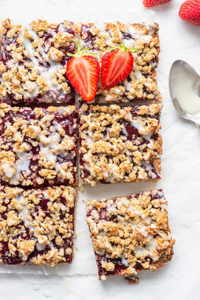 slices of strawberry oatmeal bars with white glaze and fresh berries
