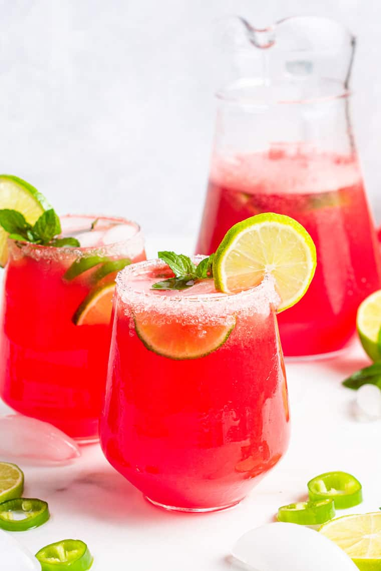 two glasses and a pitcher of watermelon margarita with lime juice and a salt rim