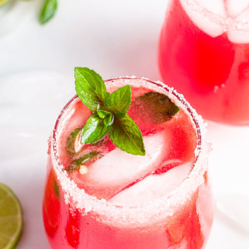 two glasses with fresh watermelon margarita on ice with mint