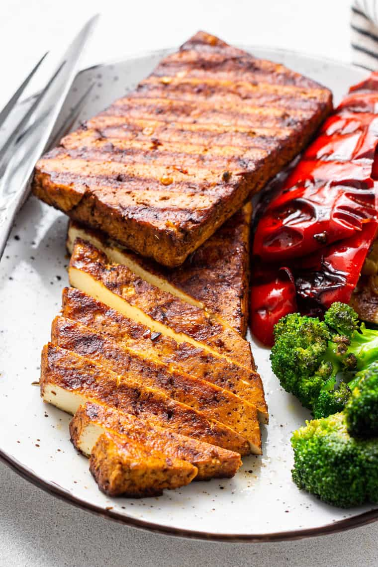 plate with two grilled tofu steaks, peppers and broccoli