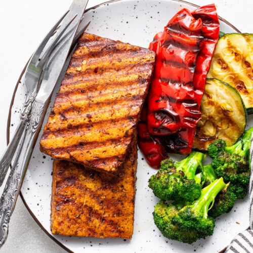 plate with grilled marinated tofu steaks, peppers, zucchini and broccoli