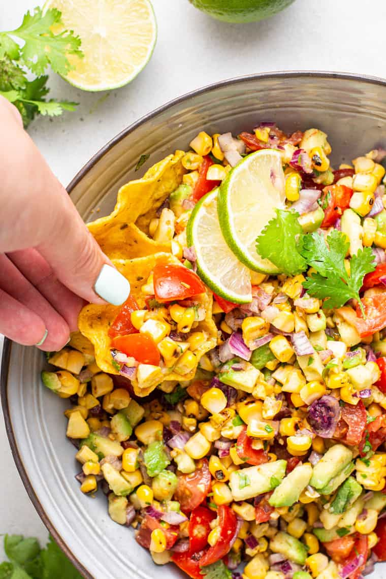 taking a chip of grilled corn avocado salsa