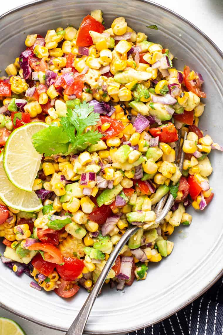 bowl of corn and avocado salsa with tomatoes and lime