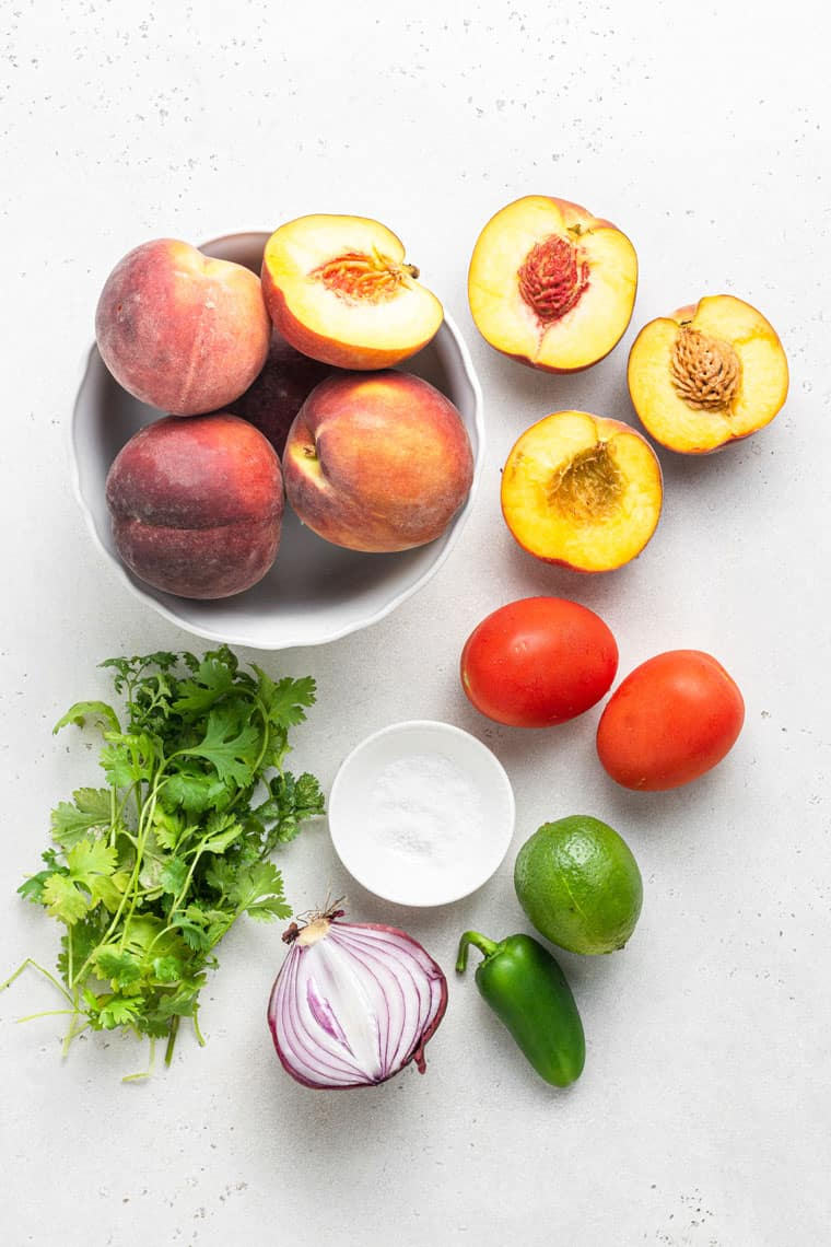 ingredients for peach salsa with tomato, jalapeno, lime and red onion