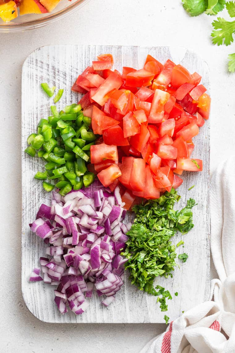 chopped tomato, jalapeno, red onion and cilantro on a cutting board