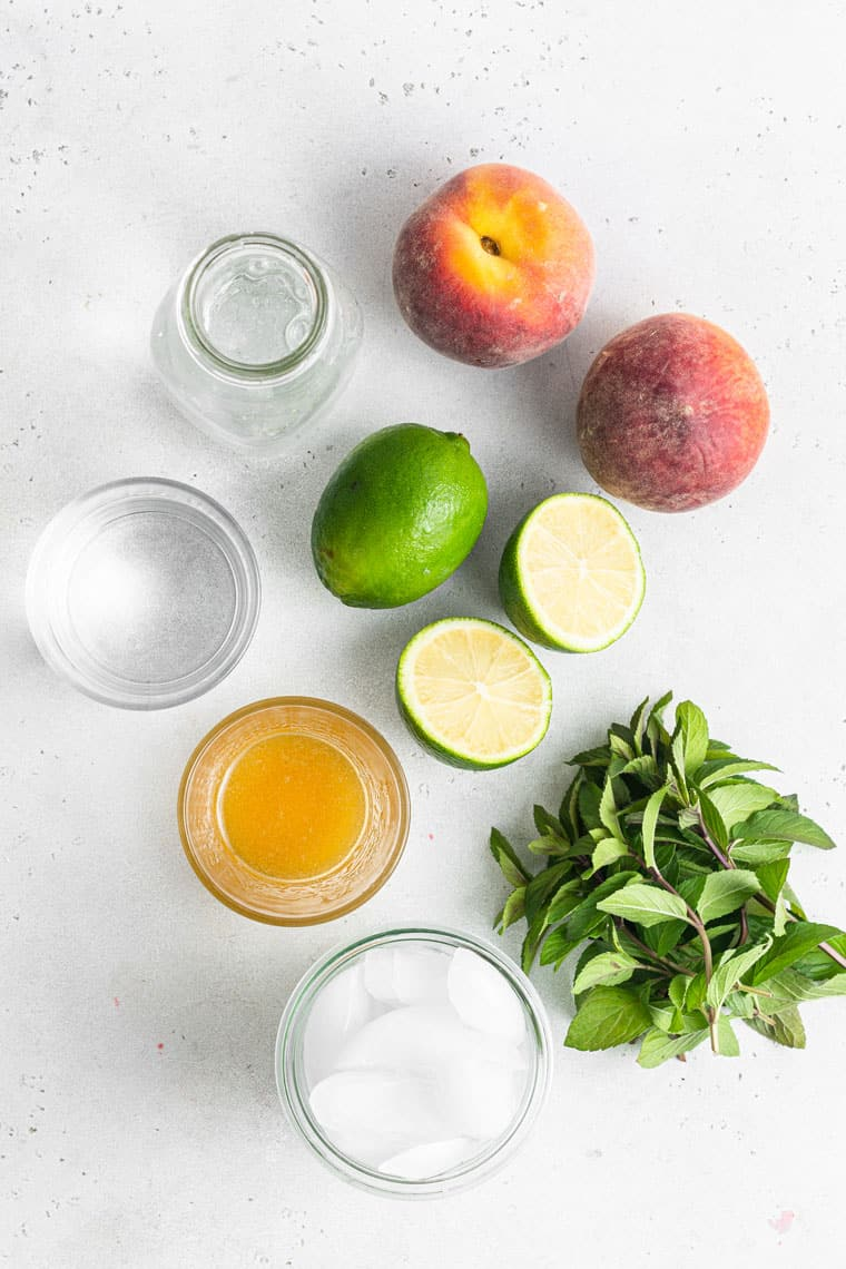 peaches, limes, mint, juice, ice and water on a counter