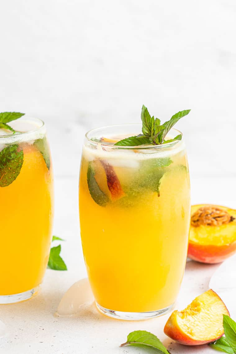 two glasses of peach mojitos with mint