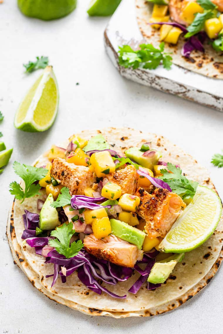 open tortilla with salmon and diced mango and fresh lime slces