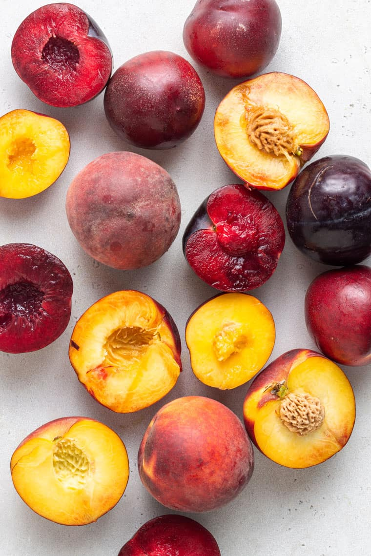 overhead of halved peaches, plums and nectarines