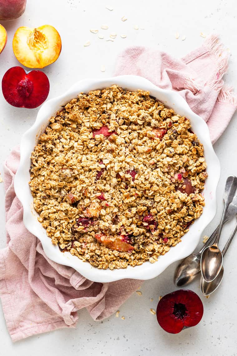 overhead of quiona crumble with stone fruit in a white baking dish