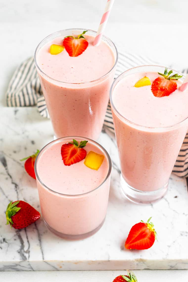 three glasses of pink smoothies with strawberries