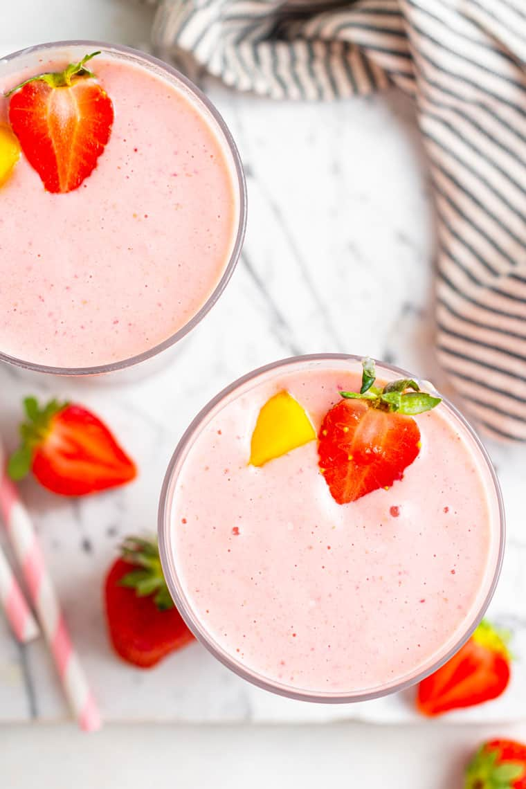 overhead of two glasses of pink smoothies with strawberries