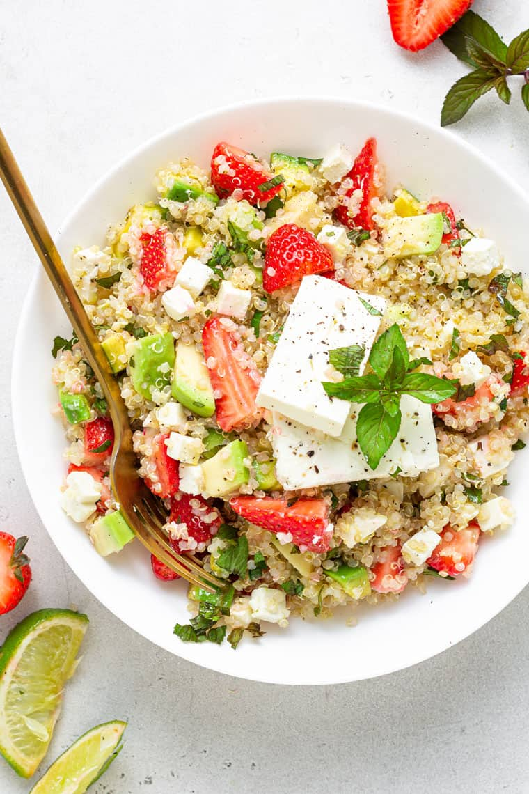 bowl of strawberry, avocado and quinoa salad with feta cheese and lime juice