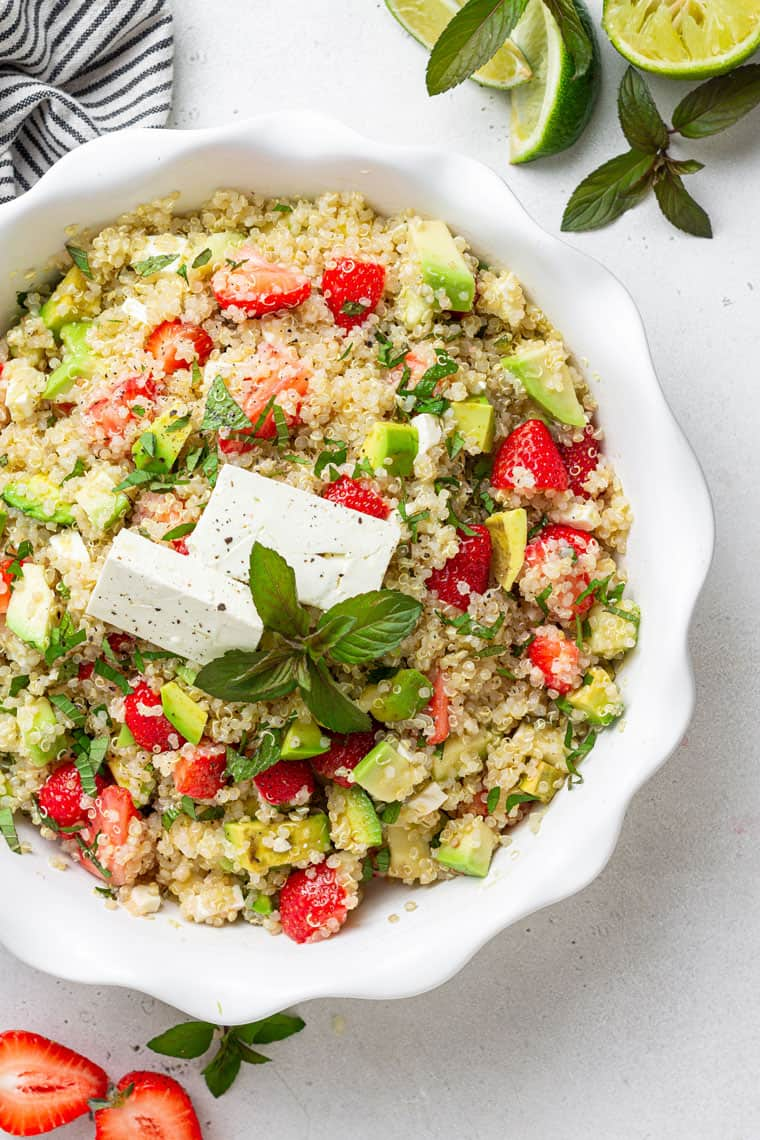 white bowl of strawberry quinoa salad with cheese, avocado and lime juice