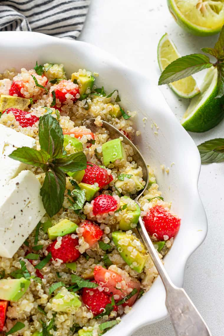 bowl of quinoa salad with fresh fruit, avocado, mint and cheese