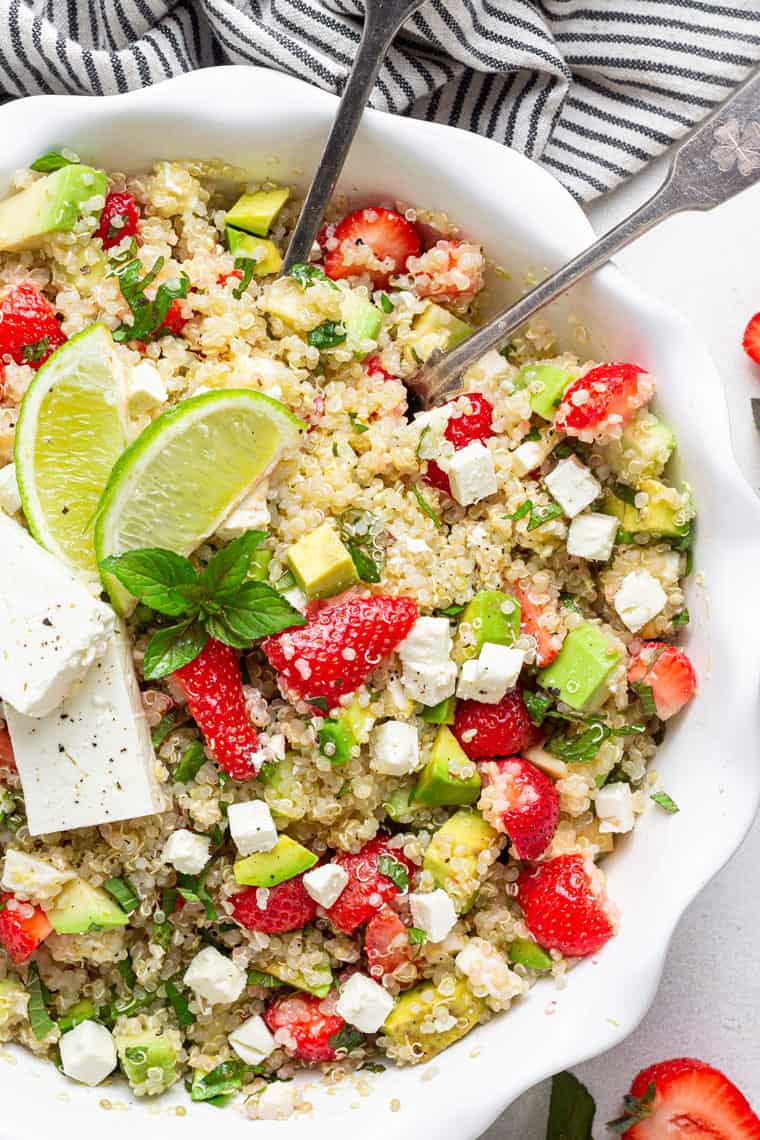 close up on a bowl of strawberry quinoa salad with avocado, cheese and lime
