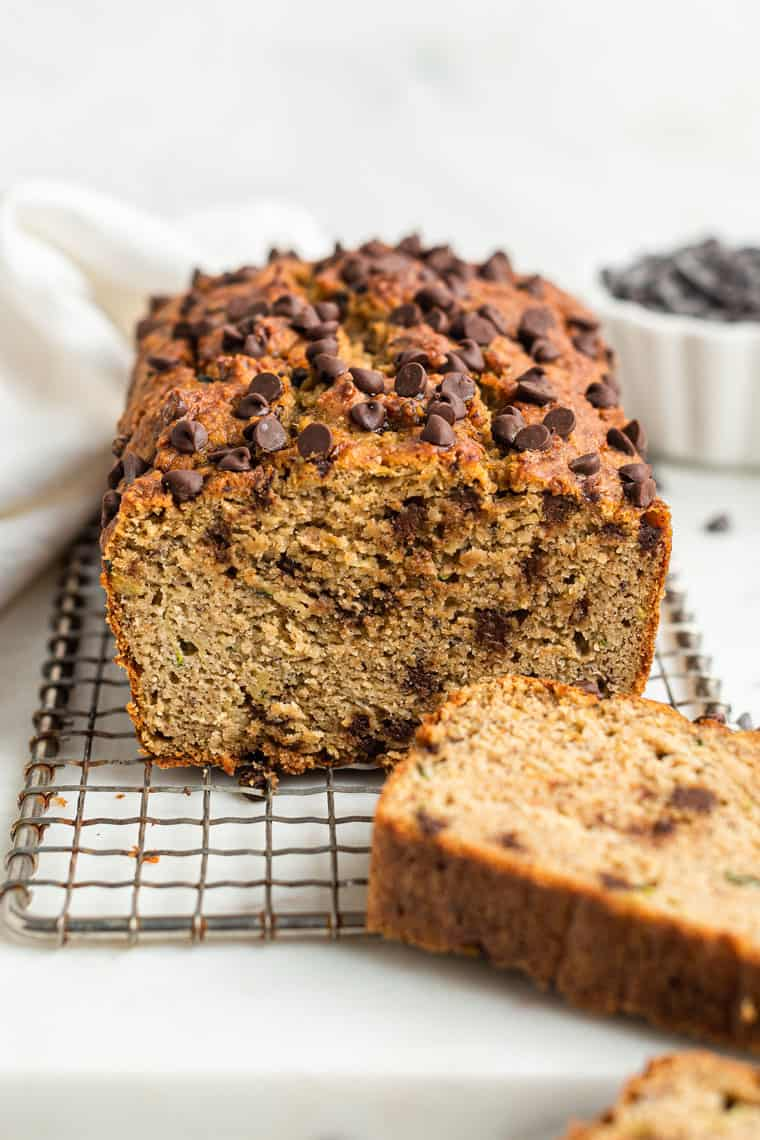whole loaf of chocolate chip zucchini bread with a slice removed on a wire rack