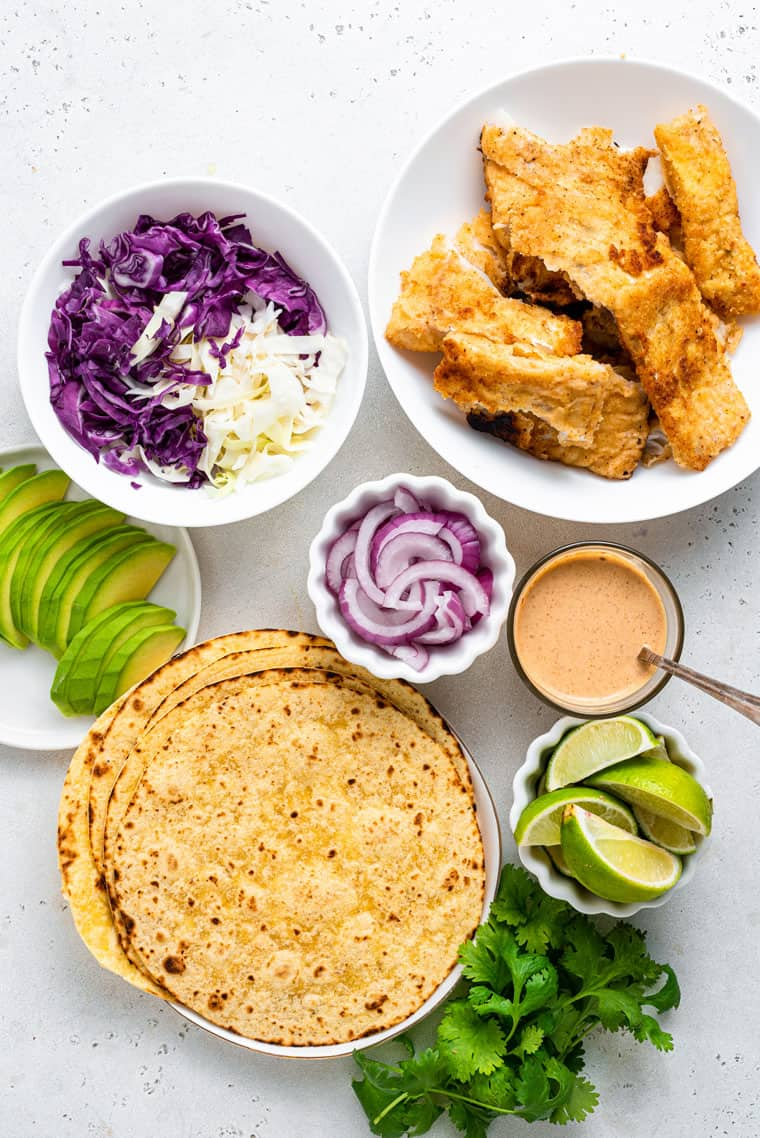 bowls with crispy breaded fish, cabbage, avocado, and tortillas