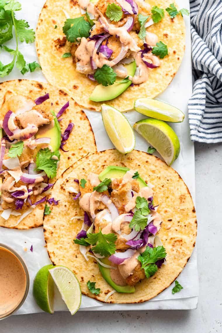 white board with three crispy fish tacos on tortillas