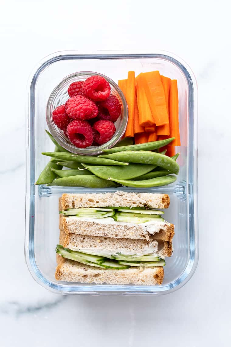 overhead of a glass bento box with fresh berries, vegetables and a sandwich