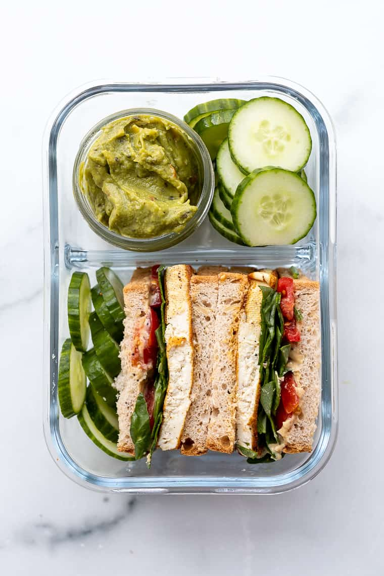 overhead of a glass bento box with cucumber and guacamole sandwiches