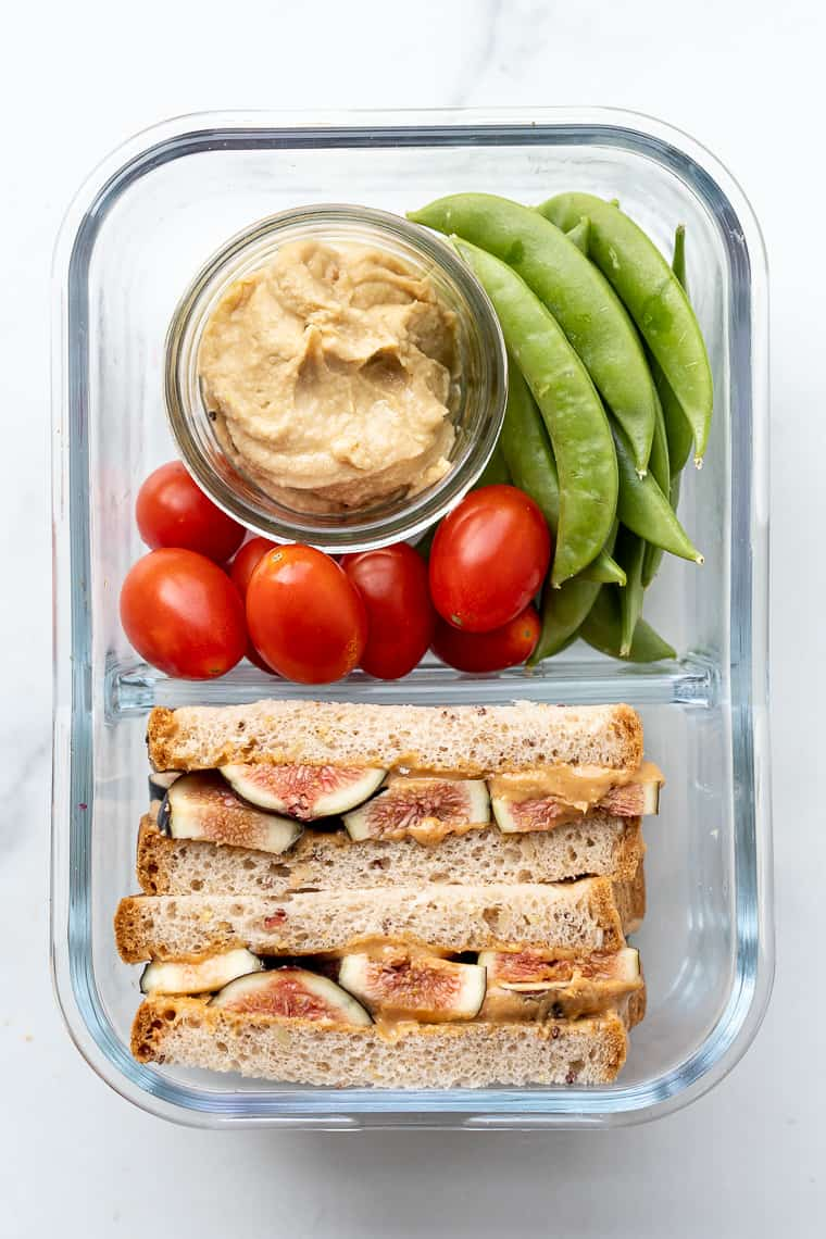 bento box with a fig and peanut butter sandwich, hummus and fresh veggies