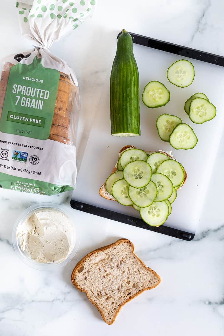 overhead of a loaf of grain bread and cucumbers on a cutting board