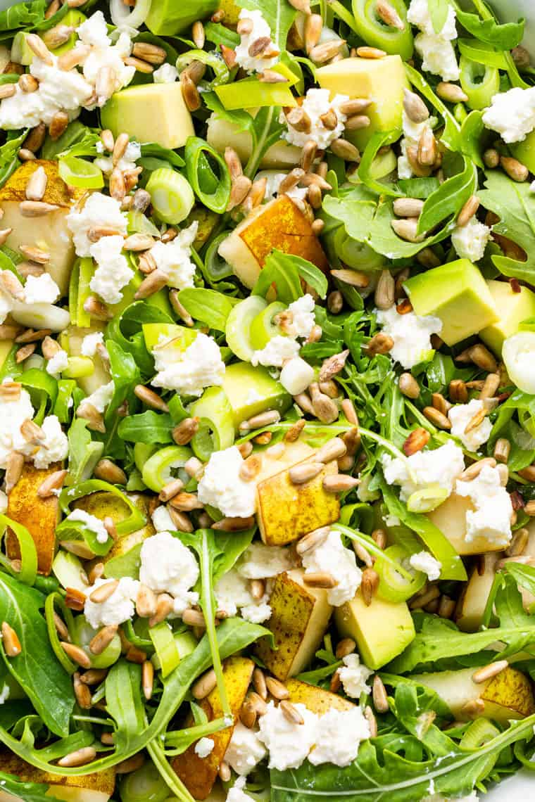 close up on arugula and pear salad with cheese and avocado