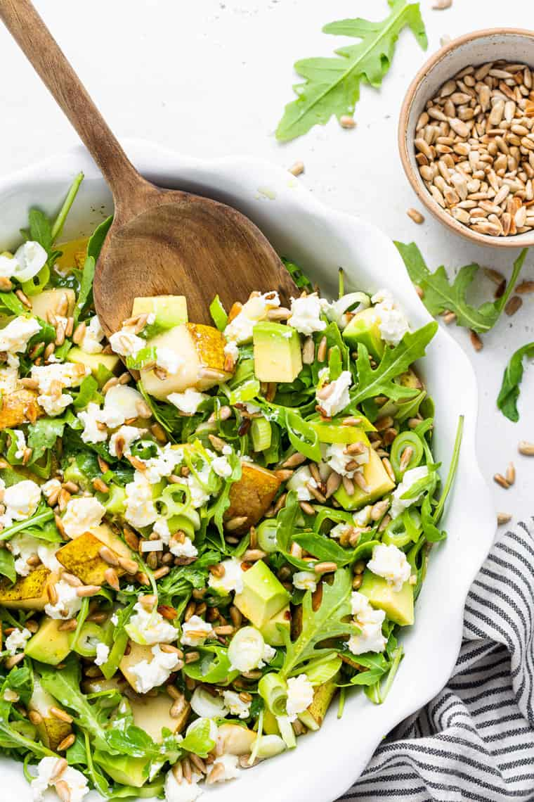 white bowl of arugula salad with pear and cheese