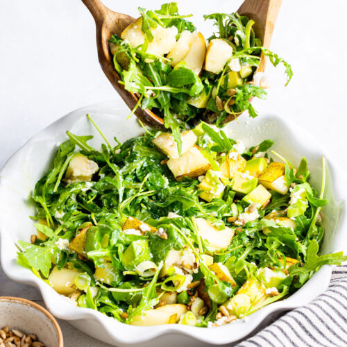 two wooden spoons tossing a salad with pear and avocado