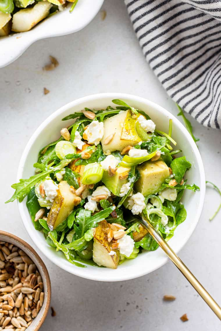 small white bowl of salad with pears, arugula, cheese and scallions