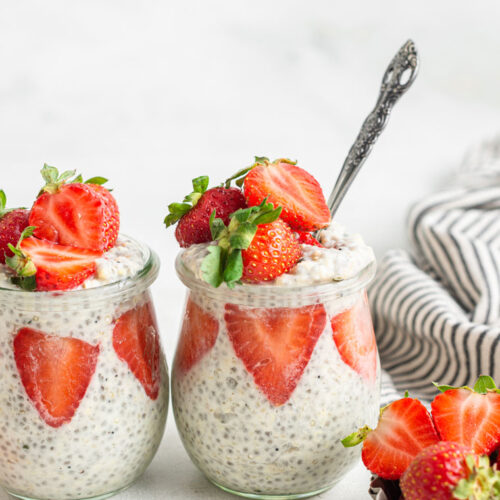 two glass jars of overnight quinoa with fresh strawberries