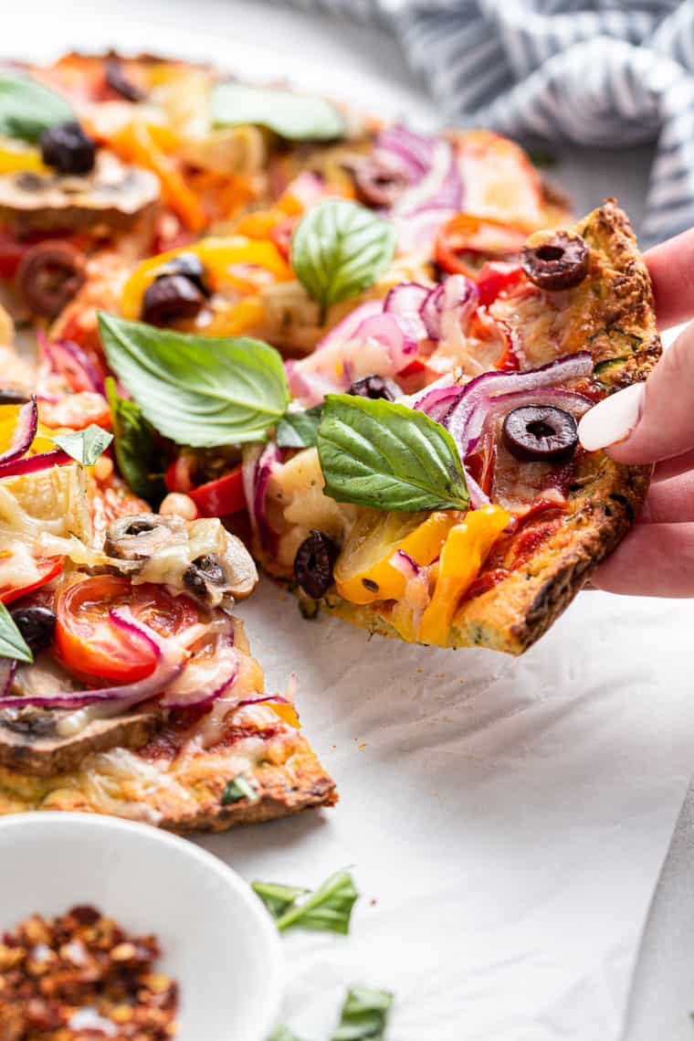 hand holding a piece of pizza with basil and olives