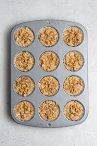 overhead of a muffin tin filled with apple batter
