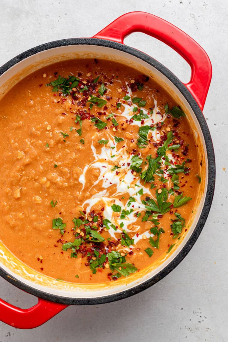overhead of a pot of tomato lentil soup with cream and herbs