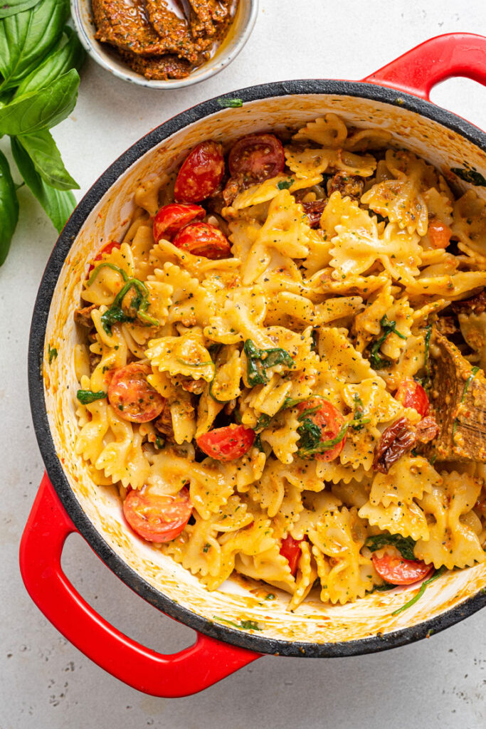 red pot of sun dried tomato pesto pasta with cherry tomatoes
