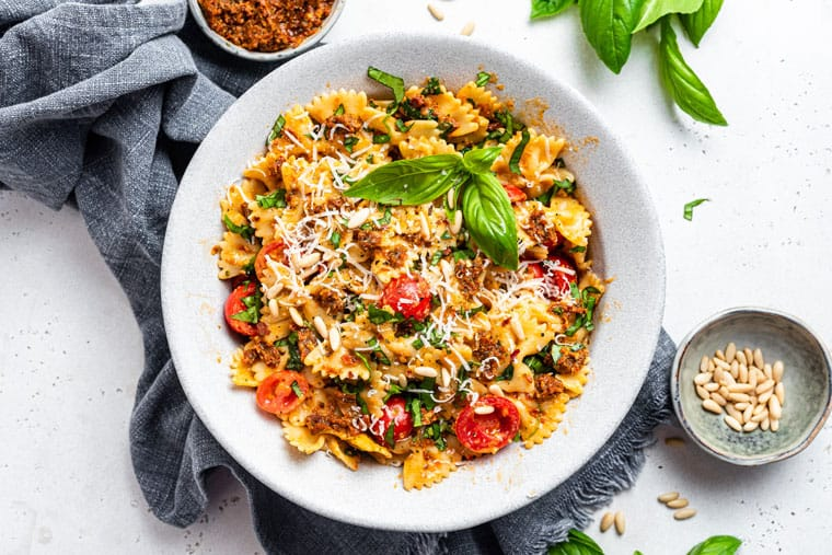 white bowl of bowtie pasta with sun dried tomato pesto