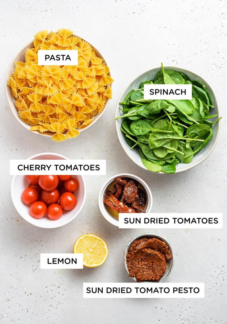 ingredients for pasta with spinach, cherry tomatoes, sundried tomatoes and lemon