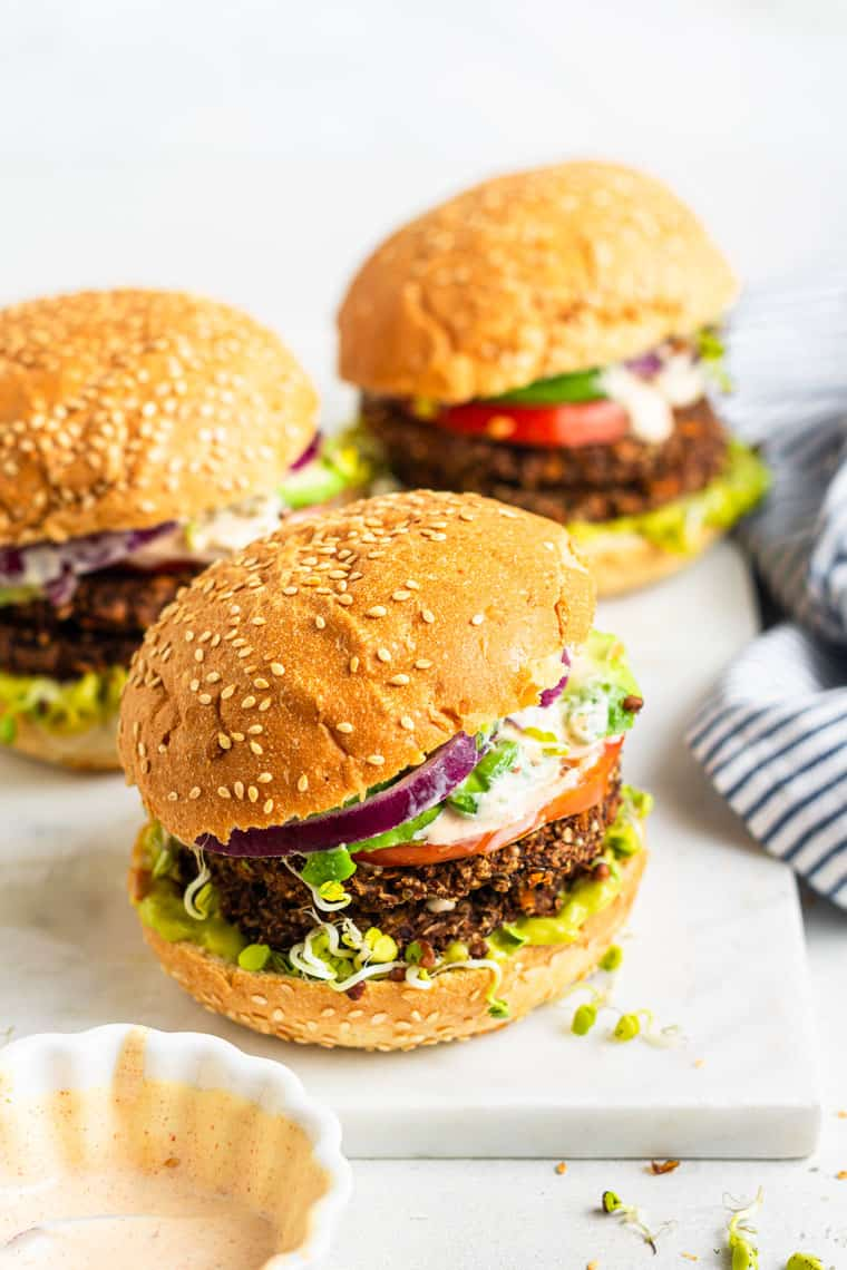 three veggie burgers on sesame seed buns with red onion and tomato