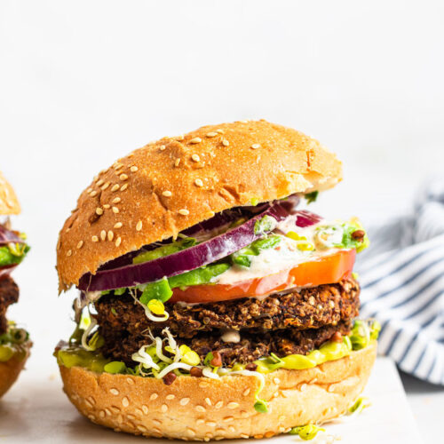 black bean burgers on a bun with onion, tomato and lettuce